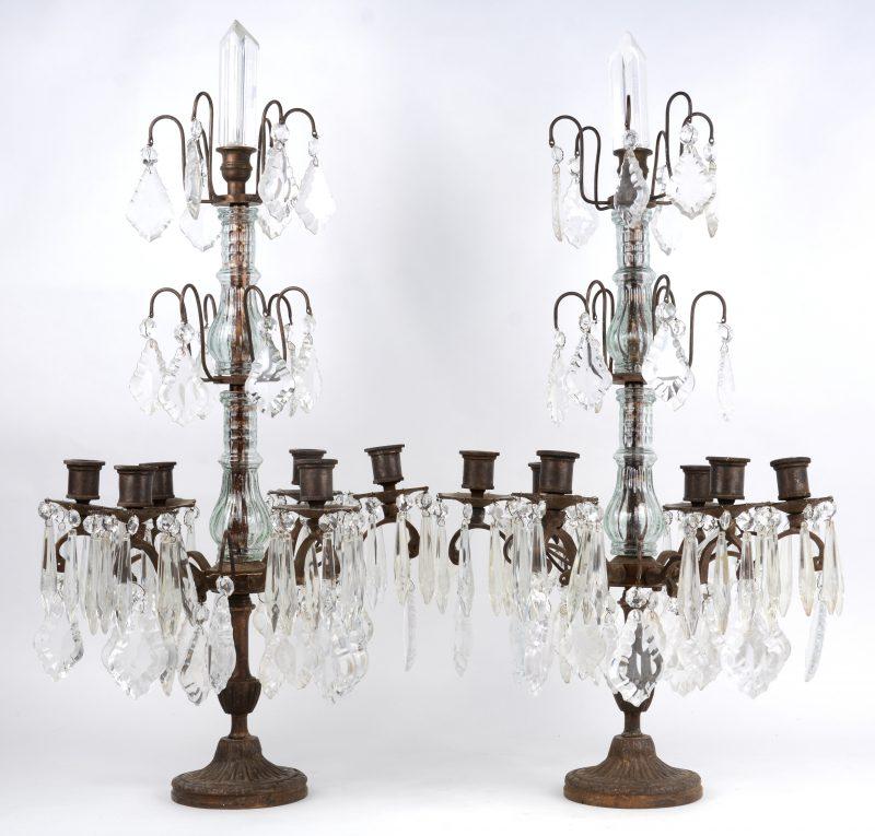 Een paar bronzen girandoles met vijf lichtpunten, versierd met geslepen kristallen pendeloques en pegels.