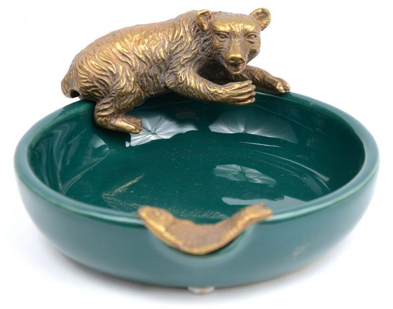 Een asbak van groen geglazuurd aardewerk, versierd met een bronzen beer en vis.