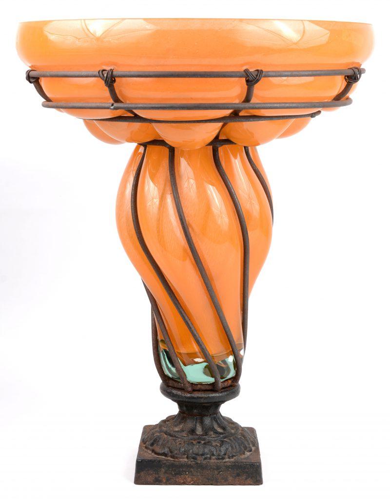 Een siervaas van oranje glas in een smeedijzeren montuur.