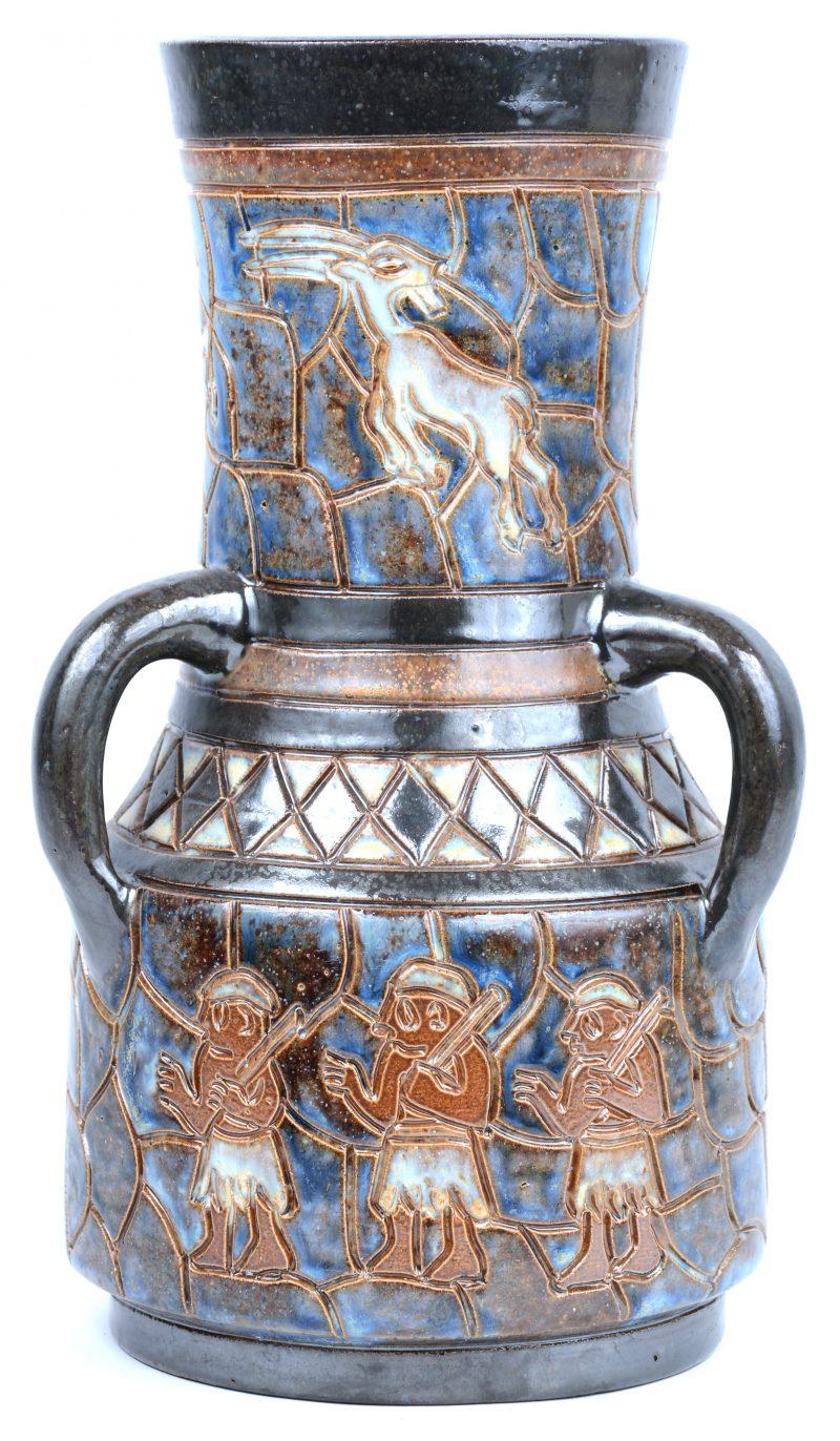 Een vaas van steengoed met drie oren en een meerkleurig geglazuurd decor met primitieve voorstellingen. Onderaan gemerkt.