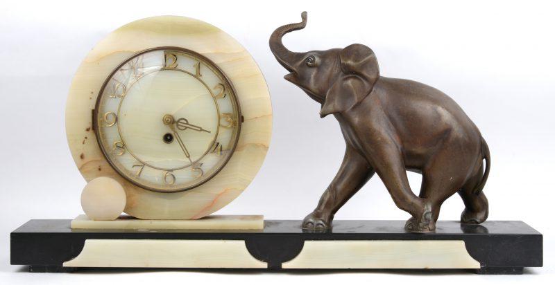 Een art deco schouwpendule van zwart marmer en onyx, versierd met een zamakken olifant.