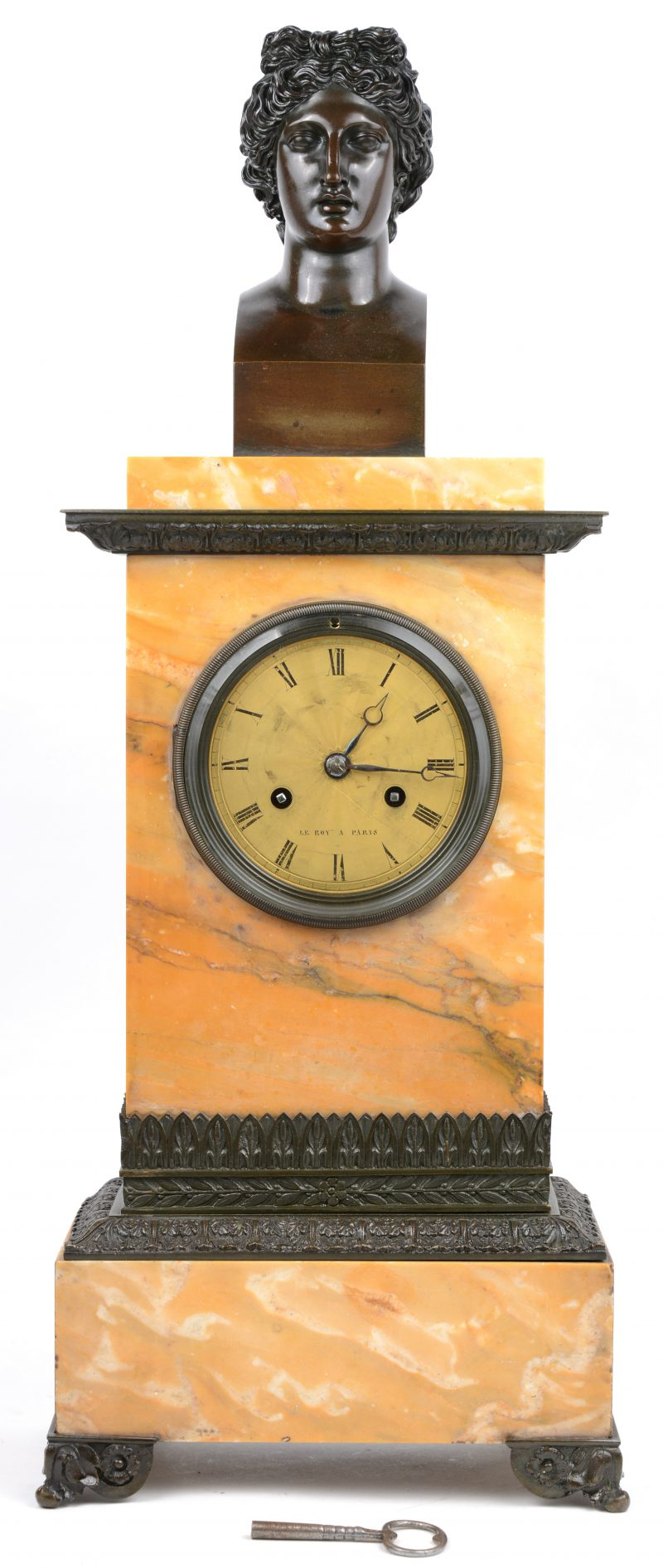 Een beige marmeren schouwpendule met bronzen pootjes, monturen en bovenaan getooid met een buste. Met sleuteljte.