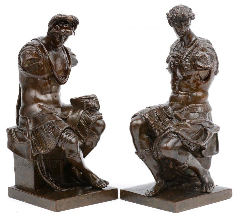 Een paar bronzen boekensteuntjes met voorstelling van zittende Romeinen.