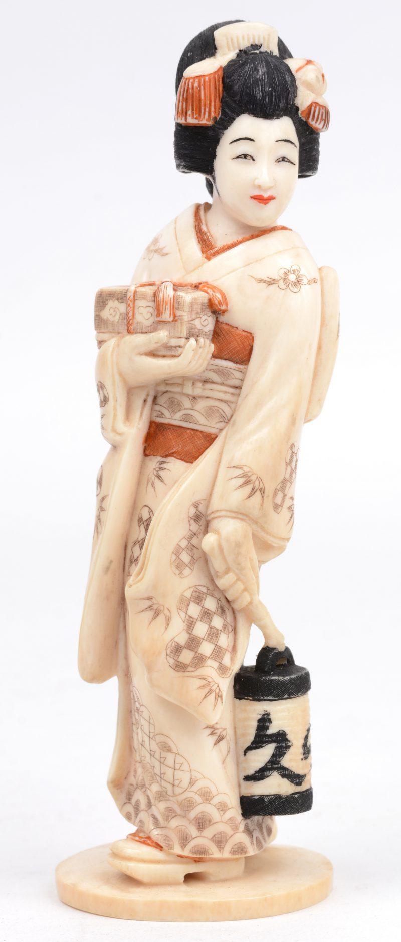 Een geisha van gesculpteerd en deels gepolychromeerd ivoor. Onderaan gesigneerd.