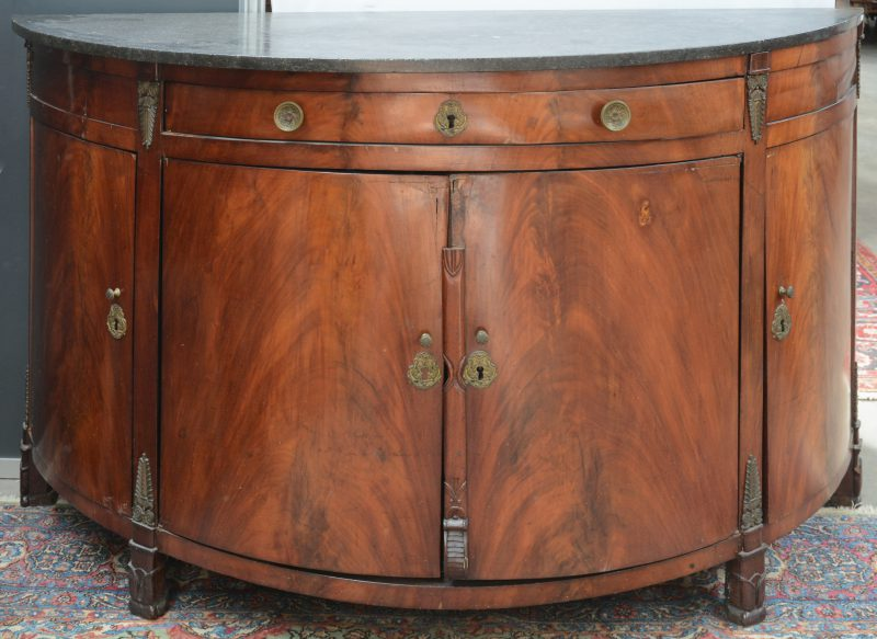Een halfrond gefineerd notenhouten buffet met vier deuren, drie laden, een marmeren blad en versierd met bronzen monturen. Tijdperk Empire.