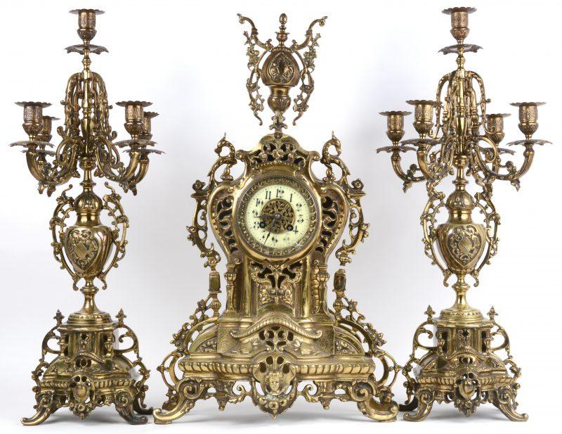 Een driedelig koperen schouwgarnituur in eclectische stijl, bestaande uit een pendule en twee vierarmige kandelaars. Glas voor de wijzeplaat gebarsten.