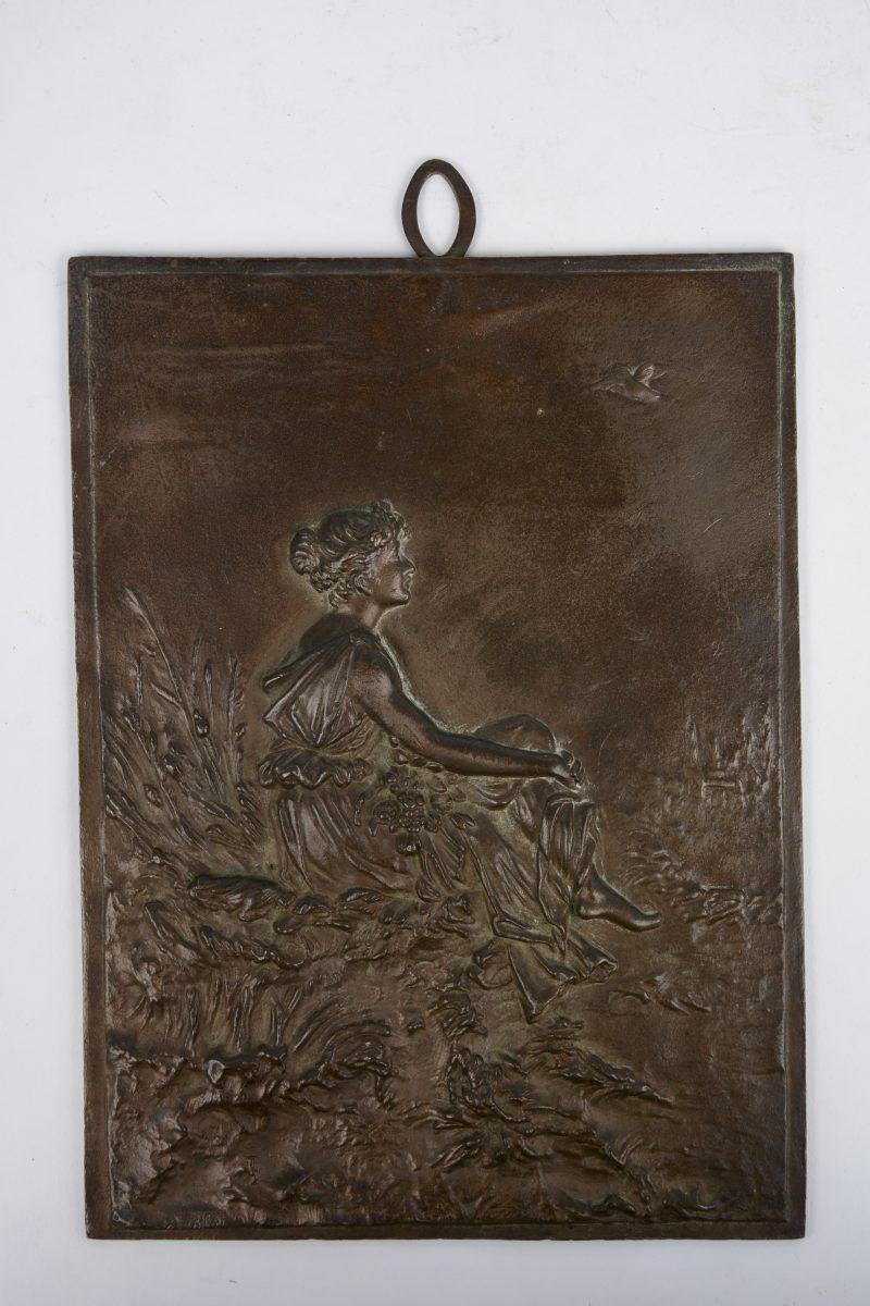 """""""Zittende vrouw in de natuur"""". Een bronzen bas-reliëf. Gesigneerd links onderaan."""