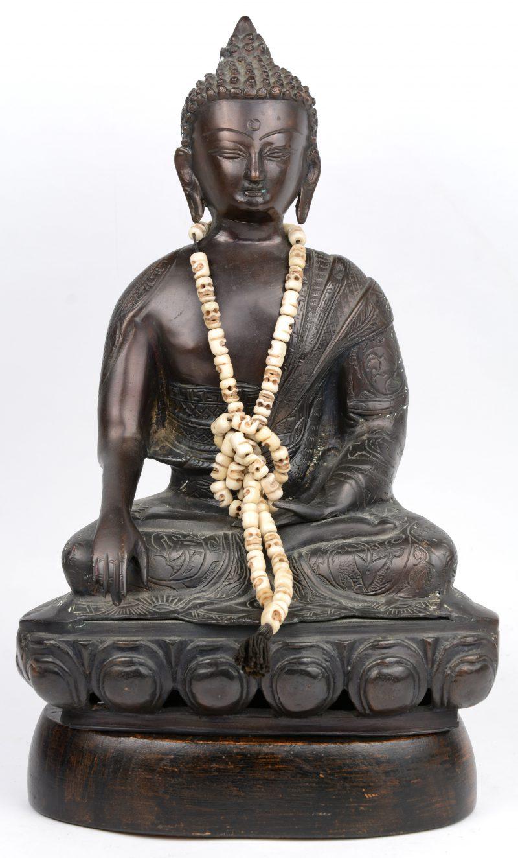 Een zittende Boeddha van brons. Met kralensnoer van gesculpteerde ivoren schedeltjes. Op losse houten sokkel.