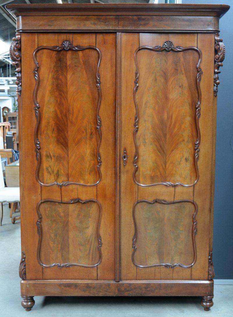 Een mahoniehouten tweedeurskast met gesculpteerde versieringen.