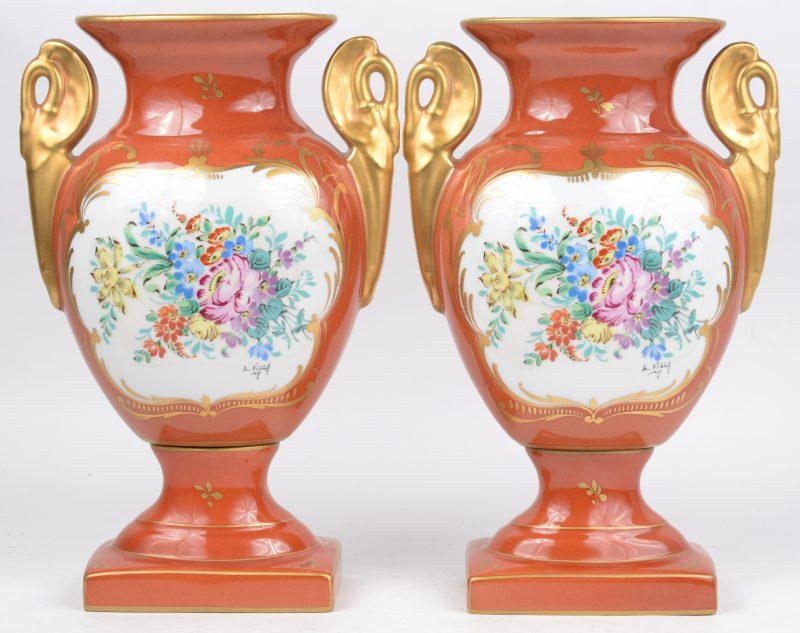 Een paar siervazen van meerkleurig en verguld porselein, versierd met handgeschilderde bloemendecors.