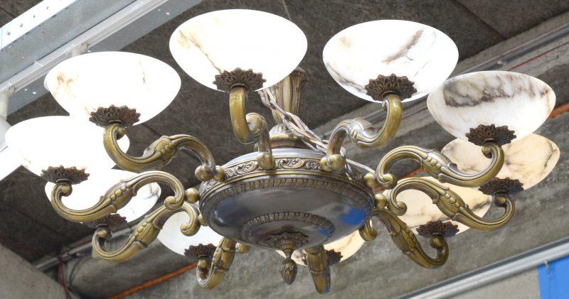 Een bronzen luchter met tien lichtpunten en albasten kappen.