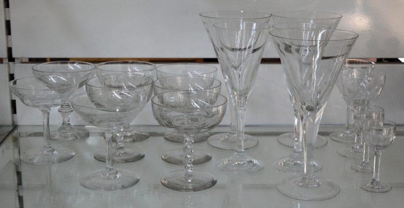 Een lotje kleurloos kristallen glazen, bestaande uit acht champagnecoupes in drie modellen, drie grote wijnglazen, twee fluiten, twee aperitiefglaasjes en twee likeurglaasjes.