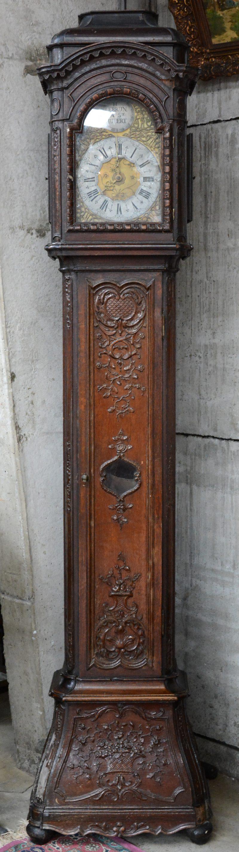 Een staande klok met gesculpteerd eikenhouten kast, versierd met bloementuilen en barokke motieven. De wijzerplaat gemerkt. Omstreeks 1800. Vernis onderaan beschadigd en kleine herstelling aan een hoekje.