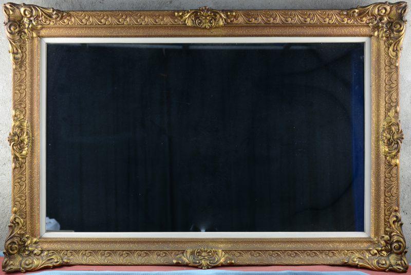 Een spiegel in goudgepatineerde houten lijst.