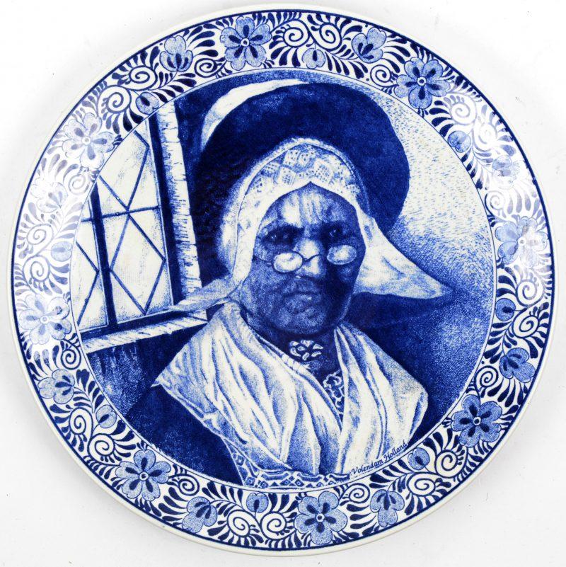 Een aardewerken bord met blauw op wit decor. Onderaan gemerkt.