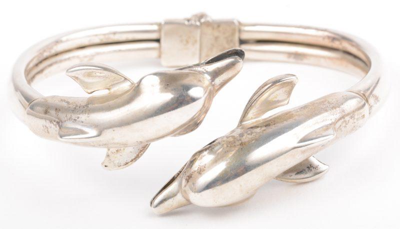 Een zilveren armband met dolfijnen.