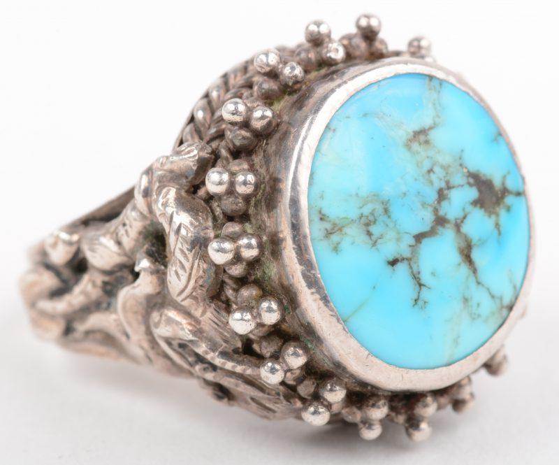 Een zilveren ring met een centrale turkoois.