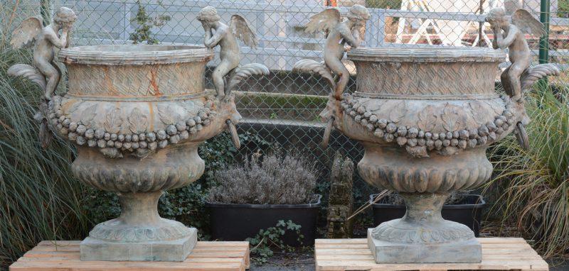 Een paar grote bronzen tuinvazen in barokke stijl versierd met engelen en guirlandes.