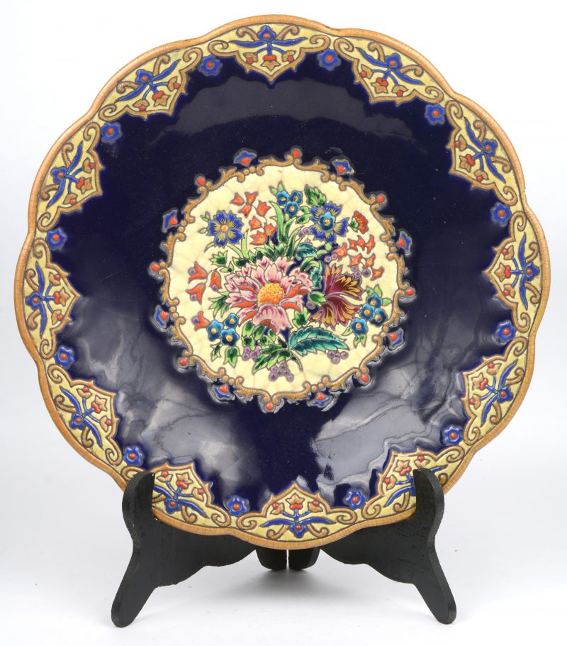 Een meerkleurig aardewerken schotel op voet met decor van M. P. Chevalier. Onderaan gemerkt. Kleine schilfer aan de basis.