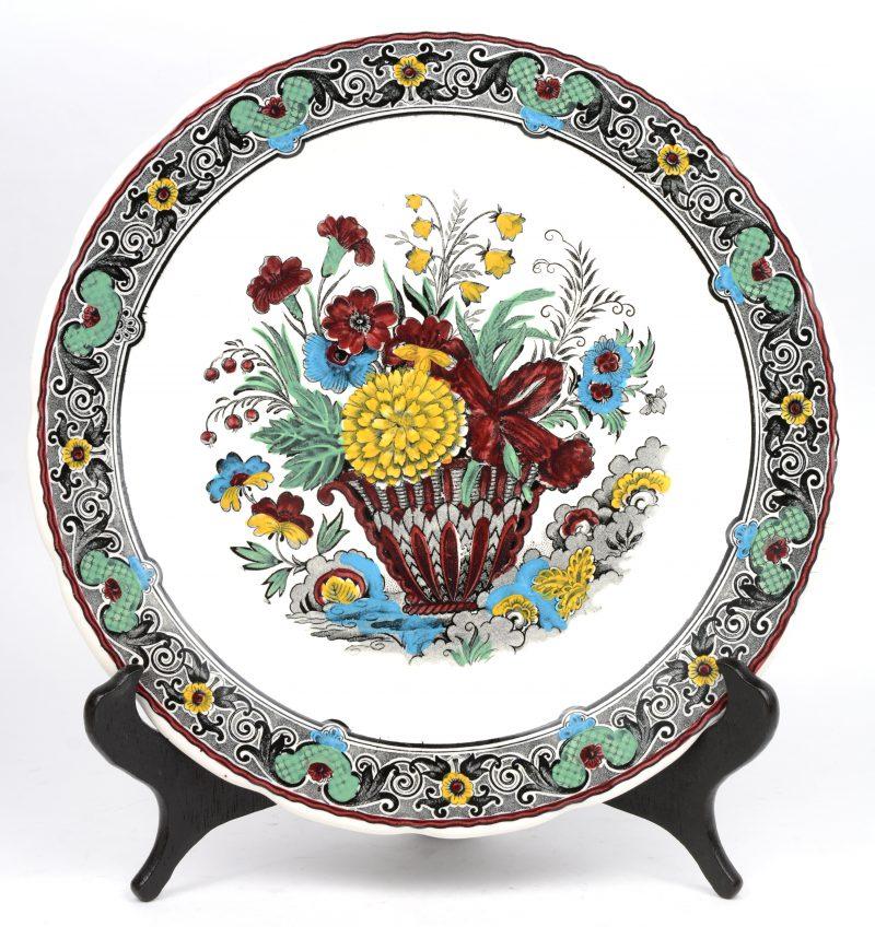 Een aardewerken sierschotel met meerkleurig bloemendecor. Onderaan gemerkt.
