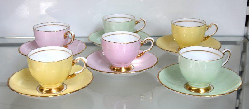Zes theekopjes met schoteltjes in geel, groen en roze. Onderaan gemerkt.