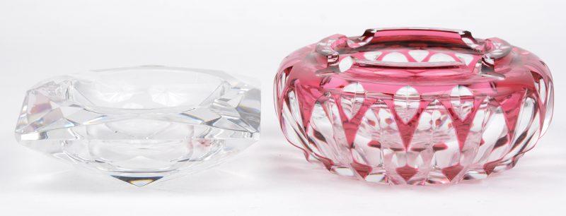 Twee geslepen kristallen asbakken, waarbij één kleurloze en één rood gedubbeld.