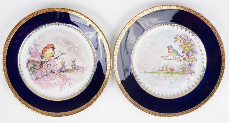 Een paar porseleinen borden met met de hand opgehoogde decors van vogels in een landschap in het plat, met kobaltblauwe vleugel en vergulde rand. Onderaan gemerkt.