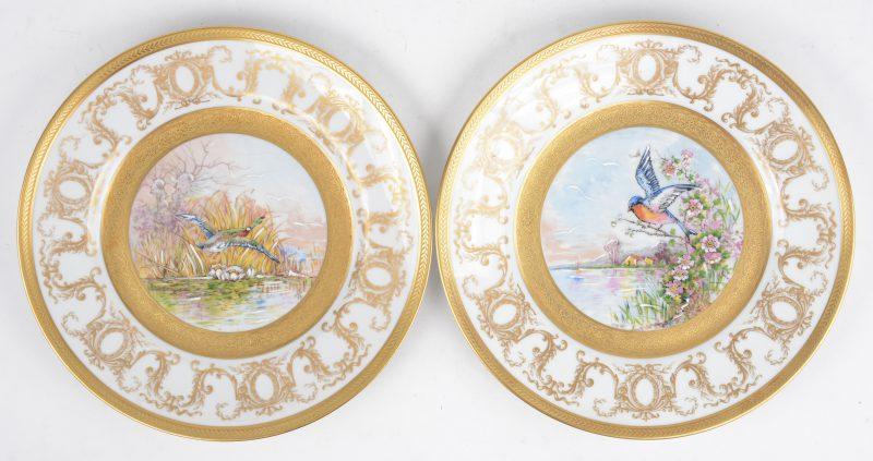 Een paar borden met met de handopgehoogd decor van vogels in een landschap en met vergulde motieven in de vleugel en de rand. onderaan gemerkt.