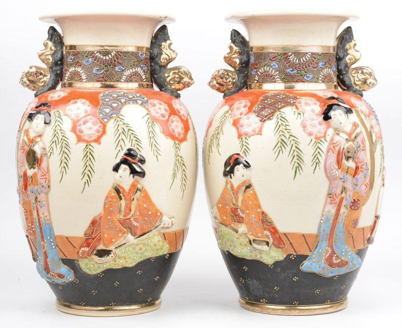Een paar vazen van Satsuma-aardewerk met een decor van geisha's in reliëf en met Fo-honden als handvatten. Onderaan gemerkt.