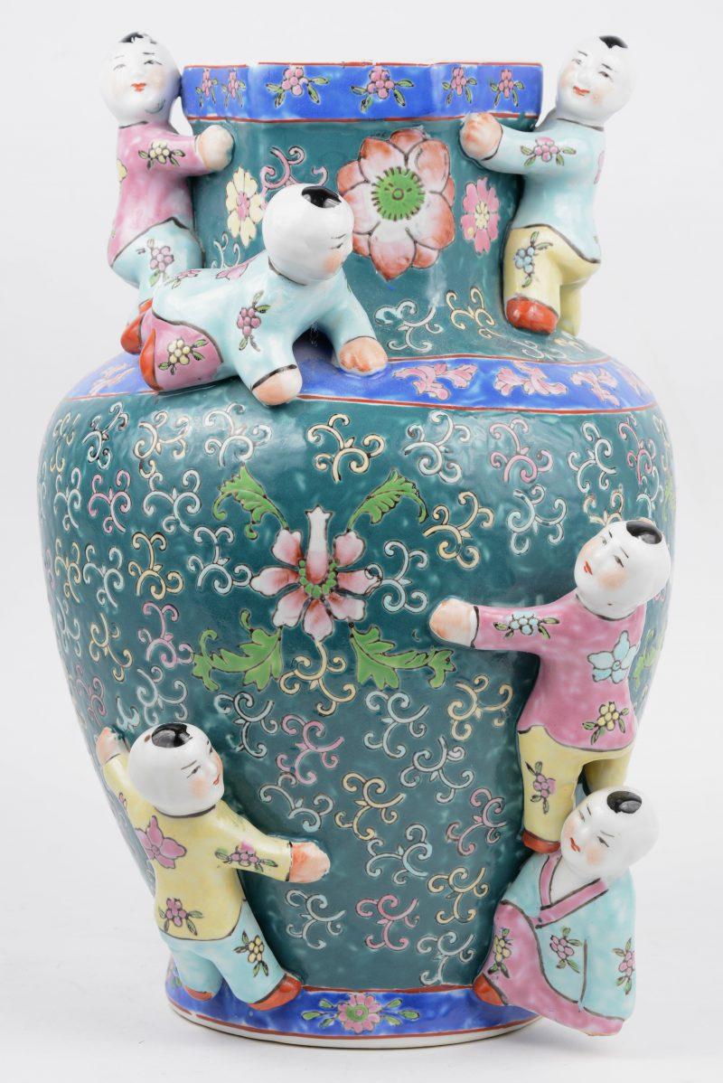Een vaas van Chinees porselein met een meerkleurig bloemendecor en met zes zotjes in hoogreliëf.