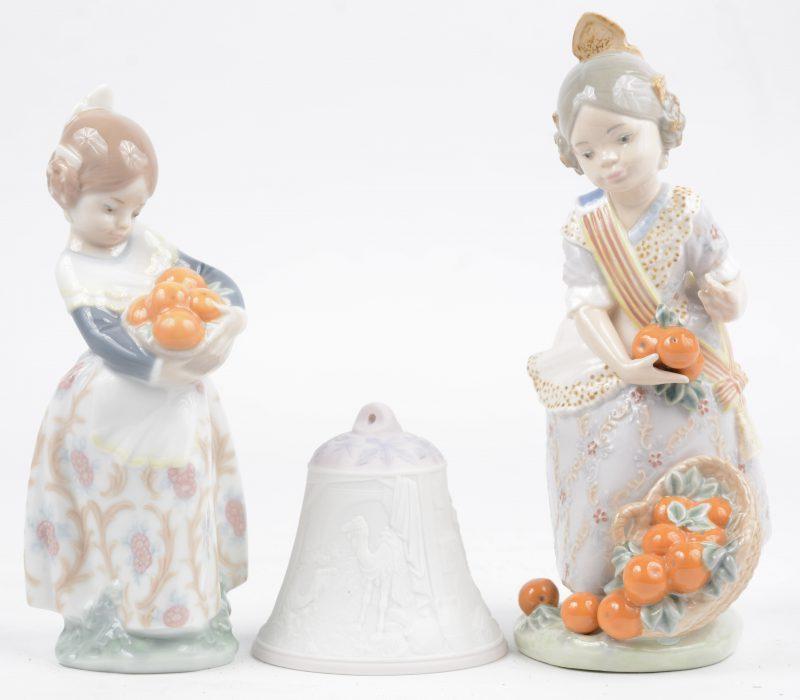 """""""Meisjes met sinaasappels"""". Twee beeldjes van meerkleurig Spaans porselein. We voegen er een biscuit kerstbelletje in origineel doosje aan toe."""
