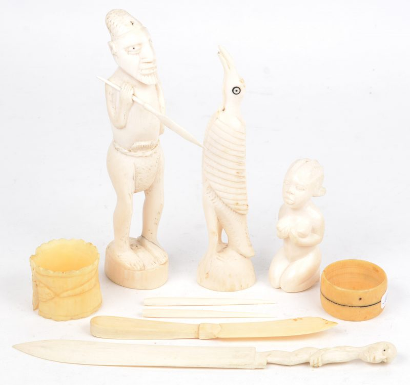 Een lot gesculpteerd Afrikaans ivoor, bestaande uit een vogel, een geknielde vrouw, een jager en twee brievenopeners. We voegen er twee benen servetringen aan toe (één beschadigd).