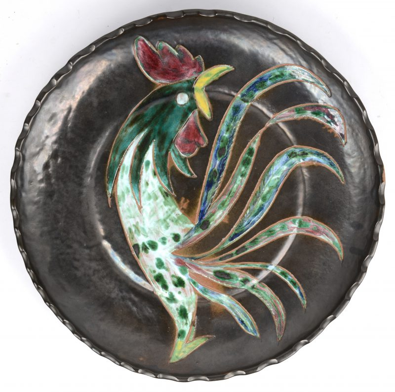 Een sierschotel van aardewerk met een meerkleurig decor van een haan. Onderaan gemerkt 'Wilfred'.