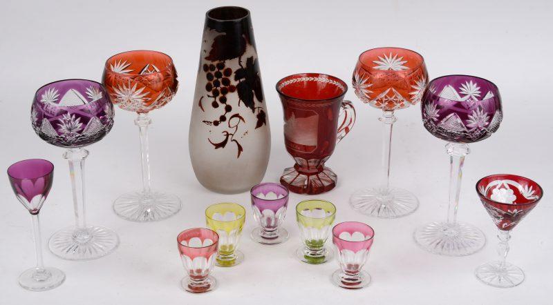 Een lot gekleurd kristal, bestaande uit twee paar geslepen wijnglazen, vijf lage borrelglaasjes, twee verschillende borrelglaasjes op voet, een souvenirglas en een glazen vaas met geëtst decor.