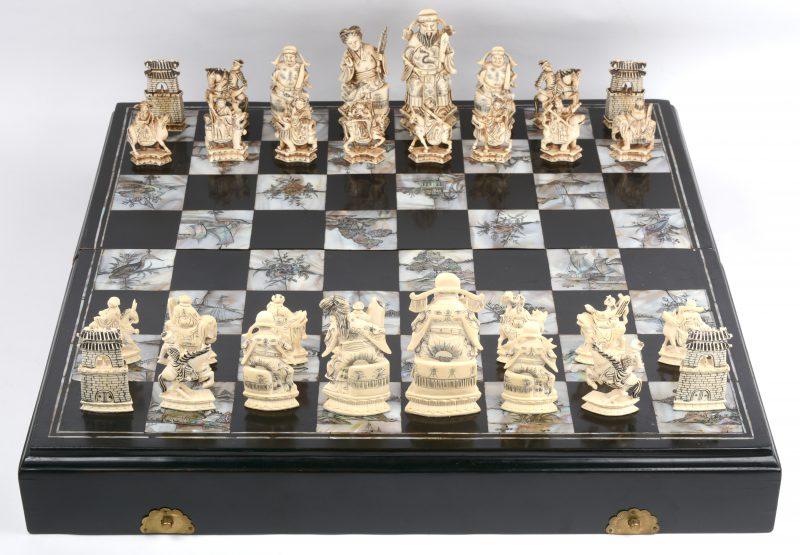 Een Chinees ivoren schaakspel, gebeeldhouwd en gegraveerd naar Qianlong voorbeeld, maar daterend uit het midden van de XXe eeuw. De zestien donkere stukken traditioneel gekleurd met thee, de zestien andere natuurlijk. Een koning meet 16 cm, een pion is 6,5 cm. De pionnen zijn gezeten op diverse dieren. het geheel wordt gepresenteerd in een zwartgelakte houten doos, ingelegd met gegraveerd parelmoer, dat de speelvelden vormt. Met Cites-attest.
