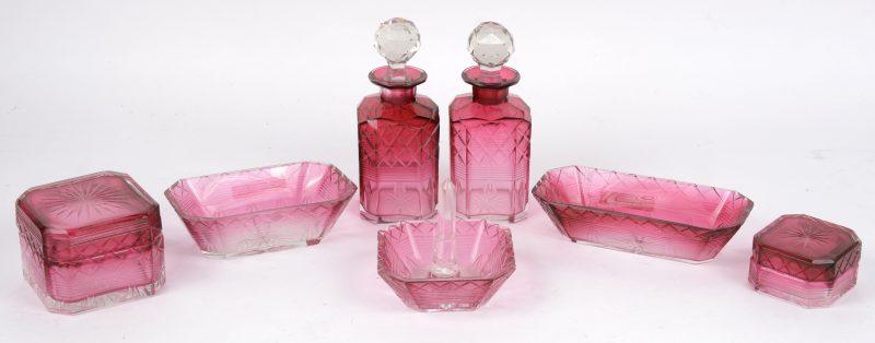 Een zevendelig toiletstelletje van geslepen roze kristal. Eén met kleine randschilfers.