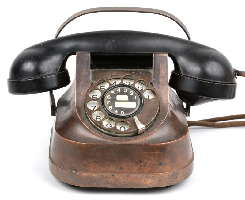 Een oude koperen draaischijftelefoon met bakelieten hoorn.