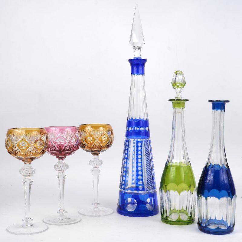 Drie kristallen wijnkaraffen van gekleurd kristal (één stop manco), evanls drie grote gekleurde wijnglazen.