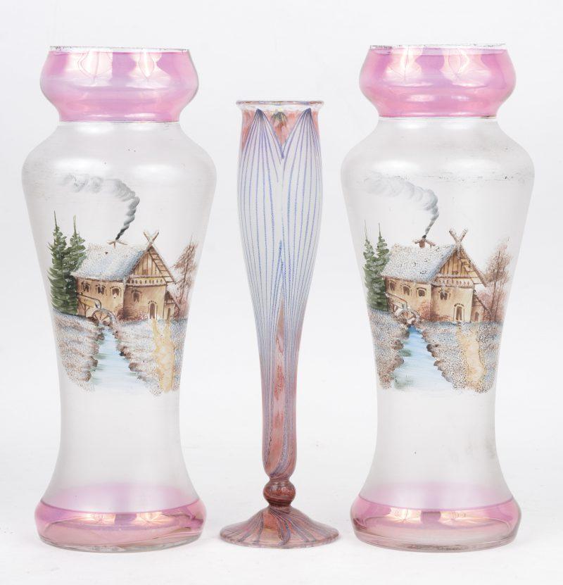 Een paar gegivreerde glazen vazen met handgeschilderd landschapdecor. Lichte slijtage aan de rand (H. 27,5 cm), evenals een lelievormig glazen soliflorvaasje (H. 24,5 cm).