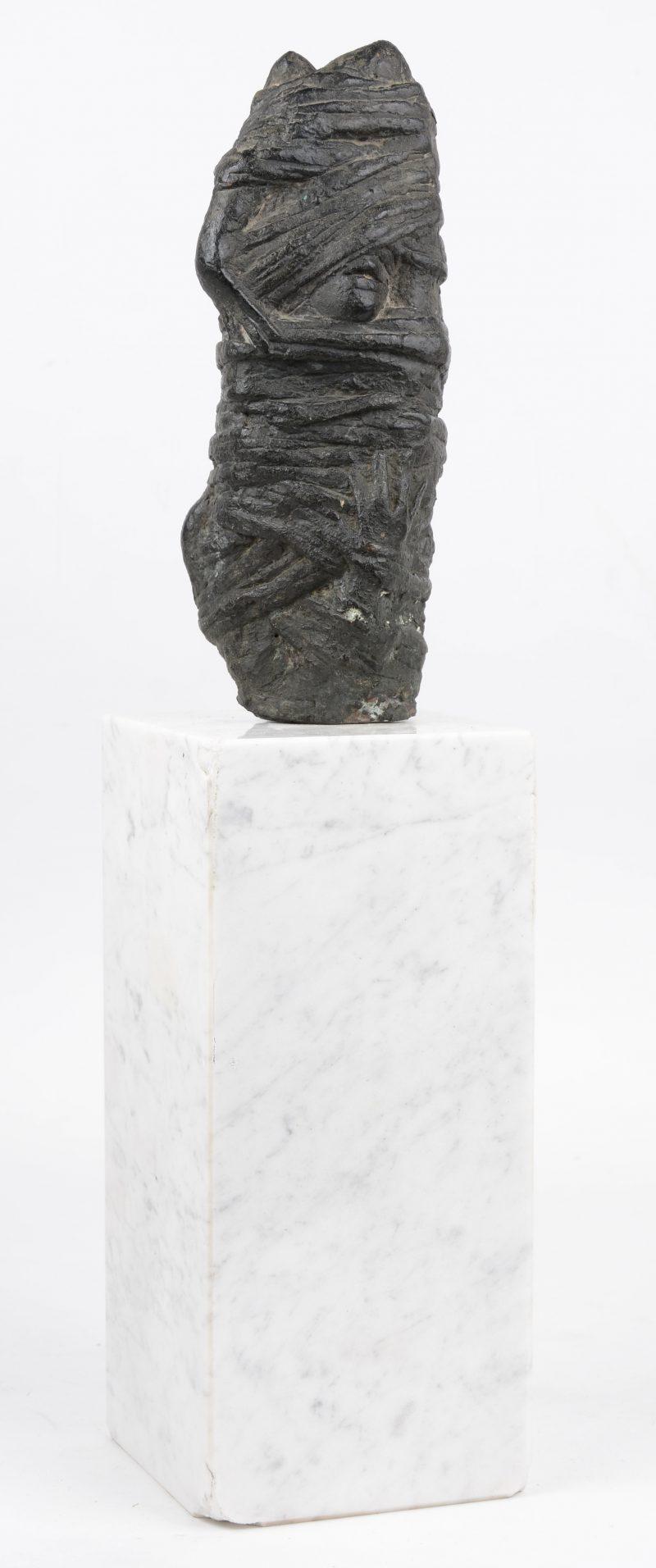"""""""Omwikkeld personnage"""". Bronzen sculptuur op witmarmeren voet."""