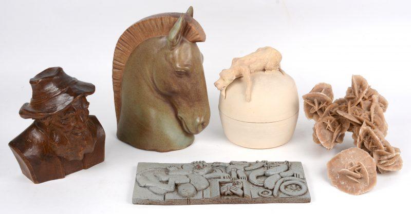 """Gevarieerd lot bestaande uit een porseleinen paardenkop van Lladro (H. 25 cm, een woestijnroos en een fractie van een woestijnroos, een terra cotta kunstwerkje in reliëf door Hugo Rabaey, een dekselpot van steengoed versierd met een hond en gemerkt """"chaf"""". Evenals een houten buste van een man met baard, gemonogrammeerd M.O."""