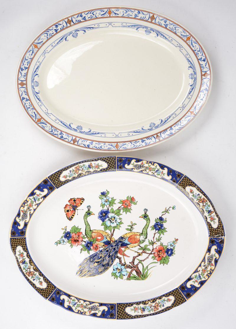 Twee verschillende ovale aardewerken schalen met een meerkleurig decor, waarbij één gemerkt van Colbert en de andere met decor van pauwen, bloemen en vlinders.