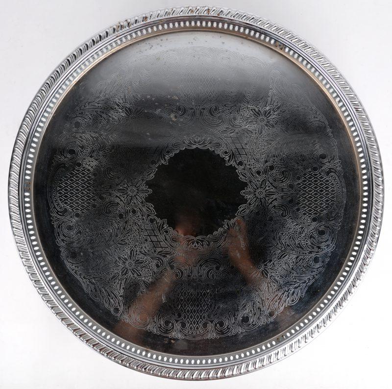 Een serveerschotel van verzilverd metaal, versierd met een gegraveerd decor. Op pootjes.