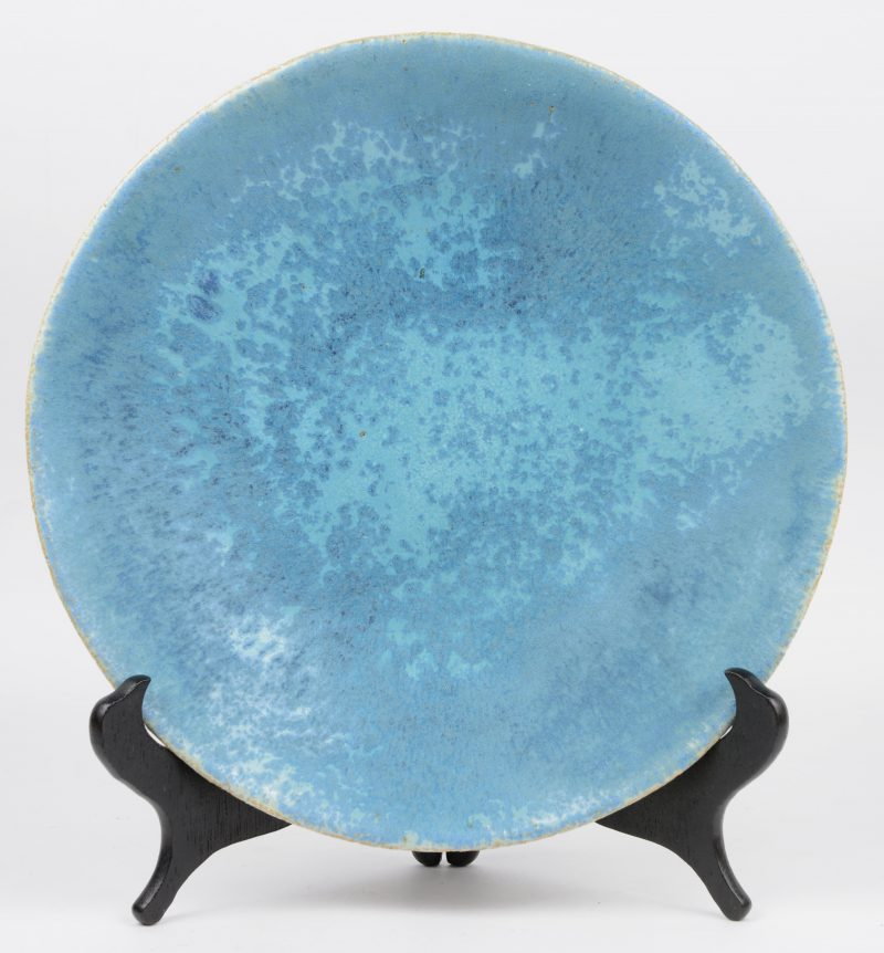 Een aardewerken sierbord met blauw glazuur. Onderaan gesigneerd.
