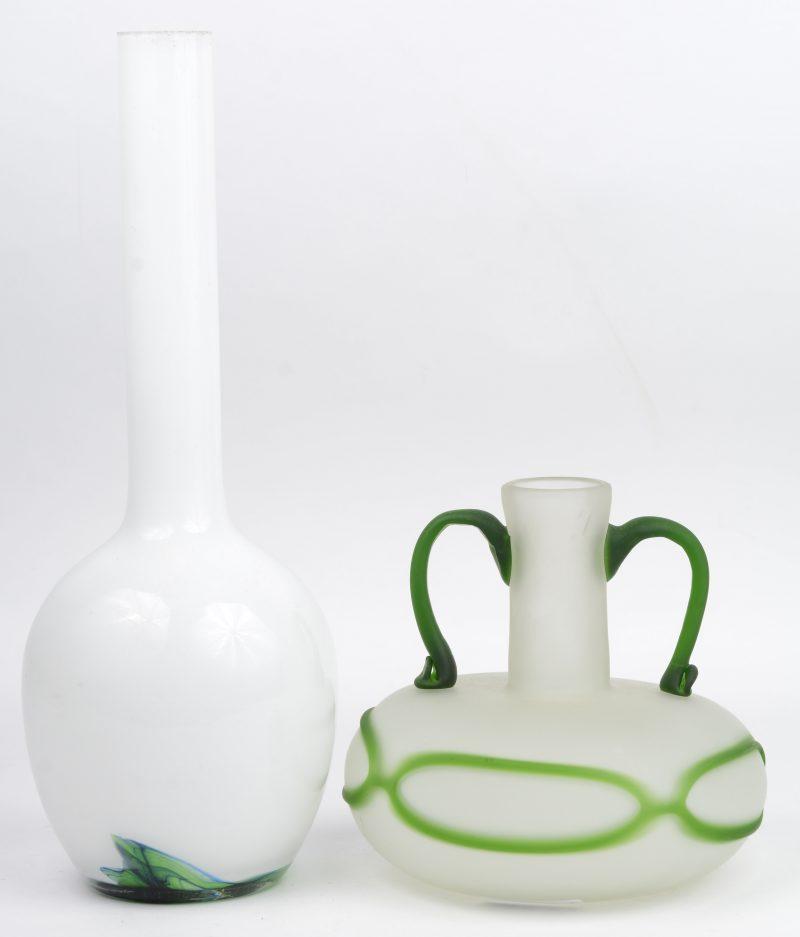 Twee verschillende glazen vazen, waarbij één gesatineerde met groen decor en handvatten en één langerekte witte met groene versiering in de voet. De tweede met randslijtage in de hals.