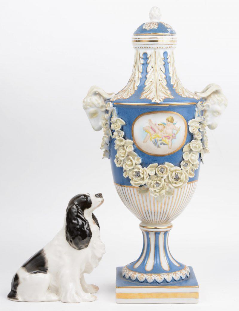 Een siervaas van meerkleurig porselein, versierd met bloemenguirlandes en ramskoppen. Onderaan gemerkt van Capodimonte. We voegen er een meerkleurig porseleinen hondje uit de Sovjetunie aan toe.