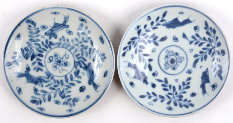 Een paar schoteltjes van Chinees porselein met een blauw en wit decor van vissen en met capucineporselein op de onderkant. Eén met zeer kleine randschilfer.