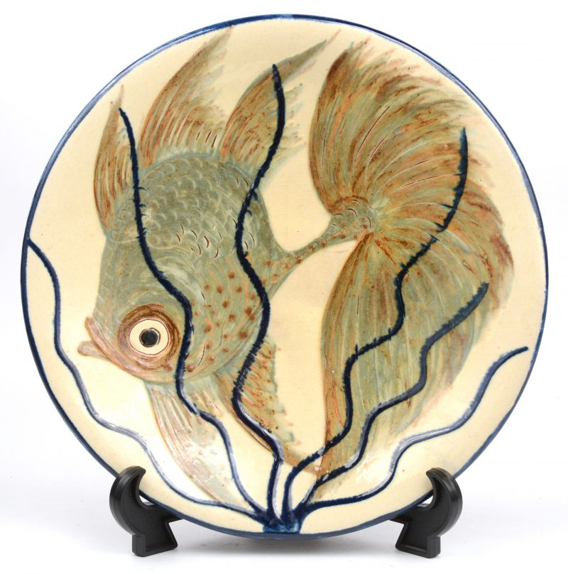 """Een geglazuurd aardewerken sierschotel met vissen in het decor. Gesigneerd onderaan """"Puigdemont""""."""