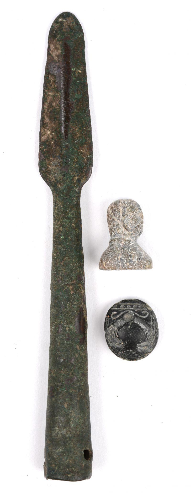 Een lot van drie archeologische vondsten. Een bronzen punt van een Romeinse pilum (L. 19 cm). Een stenen zegel (Ø 2,5 cm), Minoïsche beschaving, ca 1800 v.C. Een kalkstenen zegel (H. 3 cm), Minoïsche beschaving ca 800 v.C.