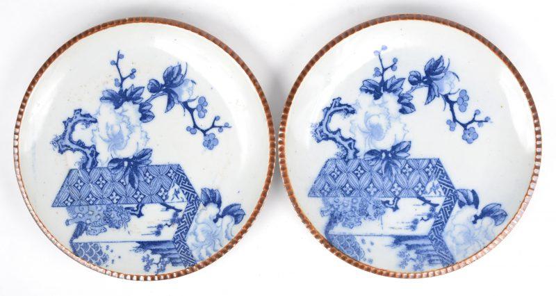 Een paar borden van Chinees porselein met een blauw op wit decor en de rand versierd met capucineglazuur.